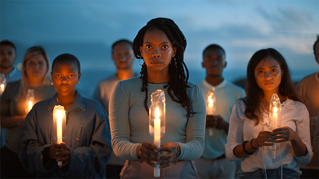 group of people gather holding candles