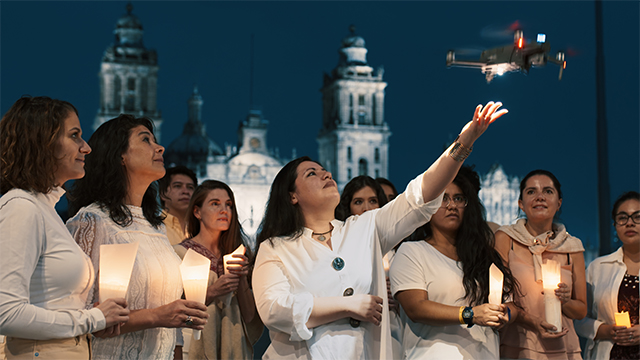Group of people holding candles gather as one releases a Celestial drone into the night sky